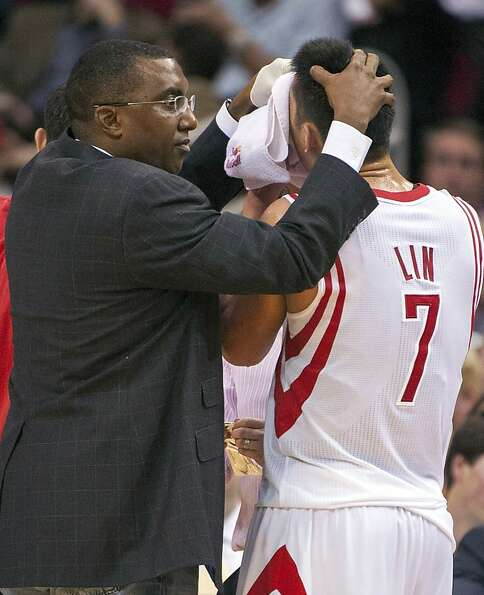 Houston Rockets trainer Keith Jones, left, helps Jeremy Lin (7) control a bloody nose after he was f
