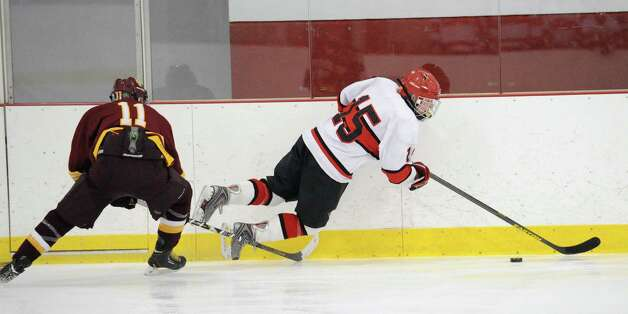 At left, Sean Hurley # 11 of St. Joseph trips Reed Brady # 15 of Greenwich during the boys high school ice hockey game between St. Joseph High School and Greenwich High School at Hamill Rink in Byram, Tuesday night, Feb. 5, 2013. St. Joseph defeated Greenwich, 5-2. Photo: Bob Luckey / Greenwich Time