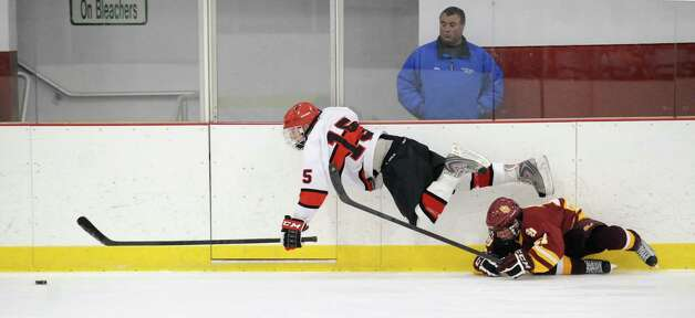 Top, Reed Brady # 15 of Greenwich gets tripped by a St. Joseph's player during the boys high school ice hockey game between St. Joseph High School and Greenwich High School at Hamill Rink in Byram, Tuesday night, Feb. 5, 2013. St. Joseph defeated Greenwich, 5-2. Photo: Bob Luckey / Greenwich Time