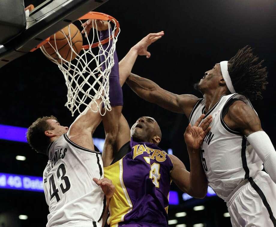The Lakers' Kobe Bryant dunks between the Nets' Kris Humphries (left) and Gerald Wallace to give L.A. an 82-80 lead. Brooklyn responded for an 83-82 lead before the Lakers closed with a 10-0 run for their third straight victory. Photo: Seth Wenig / Associated Press
