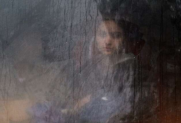 An Indian commuter looks out from a bus window while travelling during a heavy downpour in New Delhi on February 5, 2013. Heavy rains lashed the Indian capital bringing down the mercury and throwing normal life out of gear. Photo: Manan Vatsyayana, AFP/Getty Images