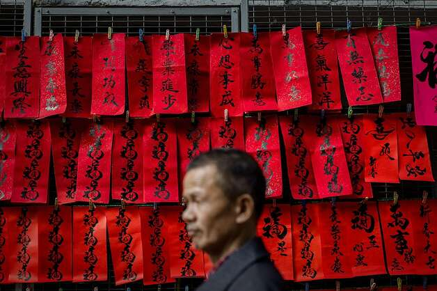 A man walks past Chinese New Year's calligraphy on red paper displayed in a street of Hong Kong on February 5, 2013. The Chinese New Year festival falls on February 10, 2013. Photo: Philippe Lopez, AFP/Getty Images