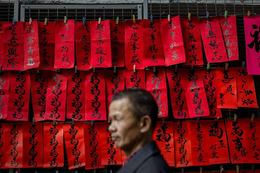 A man walks past Chinese New Year's calligraphy on red paper displayed in a street of Hong Kong on F