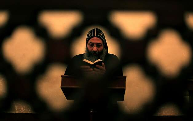 A clergyman prays during an early morning mass at  the historic al-Muharraq Monastery, a centuries-old site some 180 miles (300 kilometers) south of Cairo in the province of Assiut, Egypt, Tuesday, Feb. 5, 2013. Egypt's Coptic Christian pope sharply criticized the country's Islamist leadership in an interview with The Associated Press on Tuesday, saying the new constitution is discriminatory and Christians should not be treated as a minority. Photo: Khalil Hamra, Associated Press