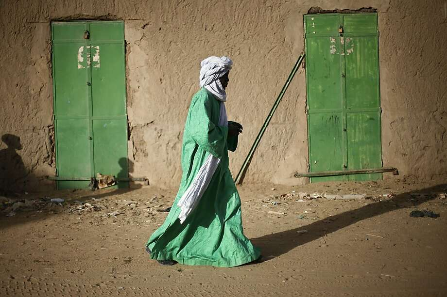 A Malian man dressed in green walks between green doors of closed shops in Gao, northern Mali, Tuesday Feb. 5, 2013.  Troops from France and Chad moved into Kidal in an effort to secure the strategic north Malian city, a French official said Tuesday, as the international force put further pressure on the Islamic extremists to push them out of their last major bastion of control in the north. Photo: Jerome Delay, Associated Press