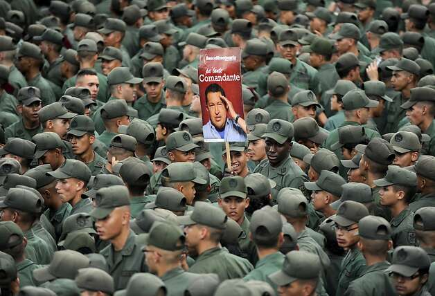 Venezuelan soldiers hold a poster of Venezuelan President Hugo Chavez during the conmemoration of the 1992 failed coup led by Hugo Chavez, who was an army lieutenant colonel, against then president Carlos Andres Perez, in Caracas, on February 4, 2013. Ailing President Hugo Chavez, who had cancer surgery in December, is doing much better and recovering, Cuban leader Fidel Castro said in remarks published Monday. Photo: Leo Ramirez, AFP/Getty Images