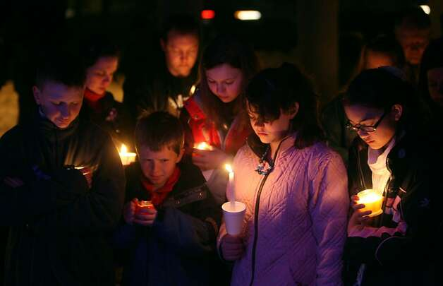 Children hold candles as they bow their heads during a prayer at a vigil for Susan Powell and her two sons, Charlie and Braden Powell, Tuesday, Feb. 5, 2013 in West Valley City, Utah. The children were killed one year ago by their father, Josh Powell, who also killed himself and blew up a house during a parental visit while a social worker was locked outside. Photo: Steve Griffin, Associated Press