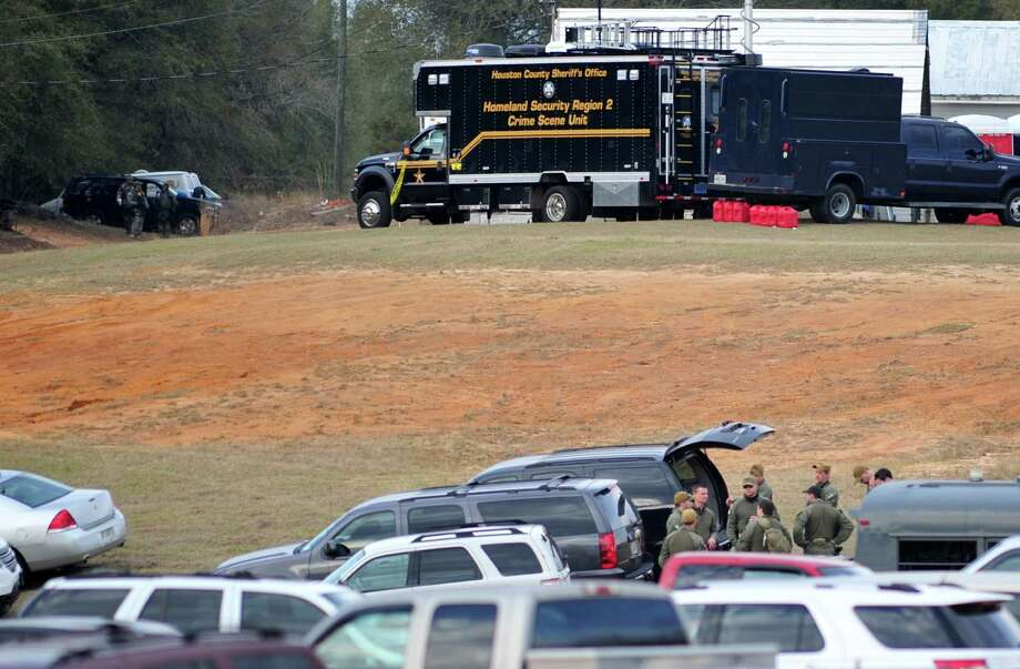 Federal and local law enforcement officers gather at their trucks after the hostage crisis ended in Midland City, Ala., on Monday afternoon, Feb. 4, 2013.  Officials say they stormed a bunker in Alabama to rescue a 5-year-old child being held hostage there after his abductor was seen with a gun. Photo: The Dothan Eagle, Jay Hare