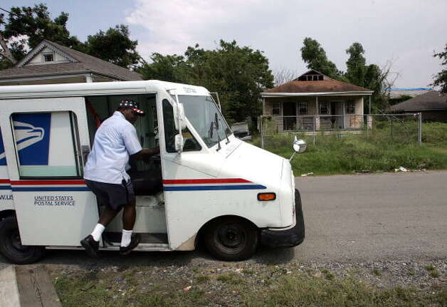NEW ORLEANS - AUGUST 23:  US Postal Service letter carrier Wayne Treaudo gets back into his truck after delivering mail to a home in the lower ninth ward August 23, 2006 in New Orleans, Louisianna. With the one year anniversary of Hurricane Katrina less than one week away, New Orleans still struggles to rebuild.  (Photo by Justin Sullivan/Getty Images) Photo: Justin Sullivan, Getty Images / 2006 Getty Images