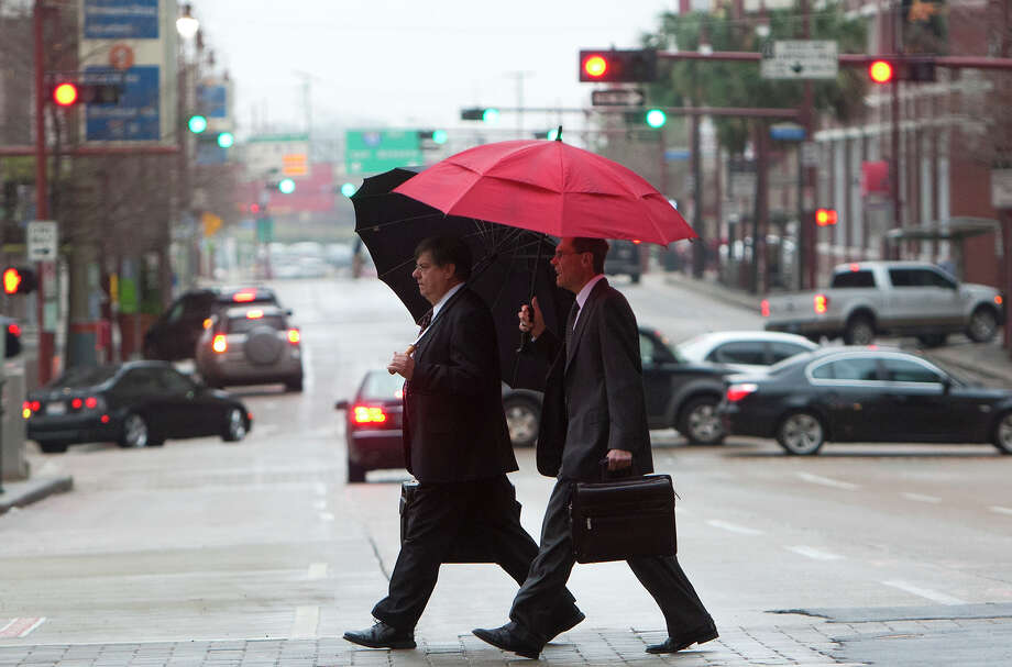 Two men shield themselves from the rain as they cross Lamar Street, Wednesday, Feb. 6, 2013, in Houston. Photo: Cody Duty, Houston Chronicle / © 2013 Houston Chronicle