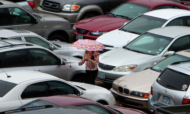 A woman shields herself from the rain as she walks through a parking lot on Milam Street, Wednesday, Feb. 6, 2013, in Houston. Photo: Cody Duty, Houston Chronicle / © 2013 Houston Chronicle