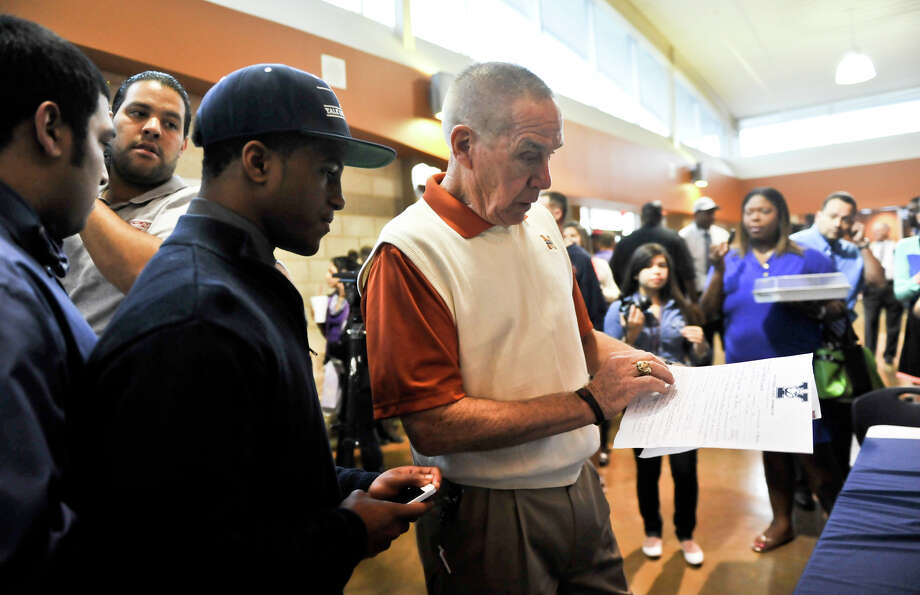 Madison High School football coach Jim Streety (right) looks over the scholarship to Yale that was signed by player Galen McCallister (left) during National Signing Day activities at the school Wednesday. Photo: Robin Jerstad