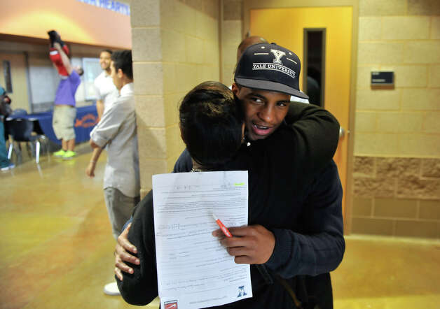 Madison High School football player Galen McAllister gets a hug from Virgina Hunter during the National Signing Day event at the school Wednesday. McAllister has signed to play at Yale next year. Photo: Robin Jerstad