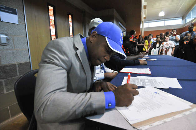Madison High School football player Marquis Warford signs his scholarship to the University of Memphis during a National Signing Day ceremony at the school Wednesday. Photo: Robin Jerstad