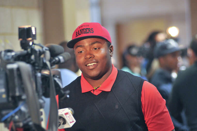 Madison High School football player Jalen Privott speaks to a TV reporter after signing a footbal