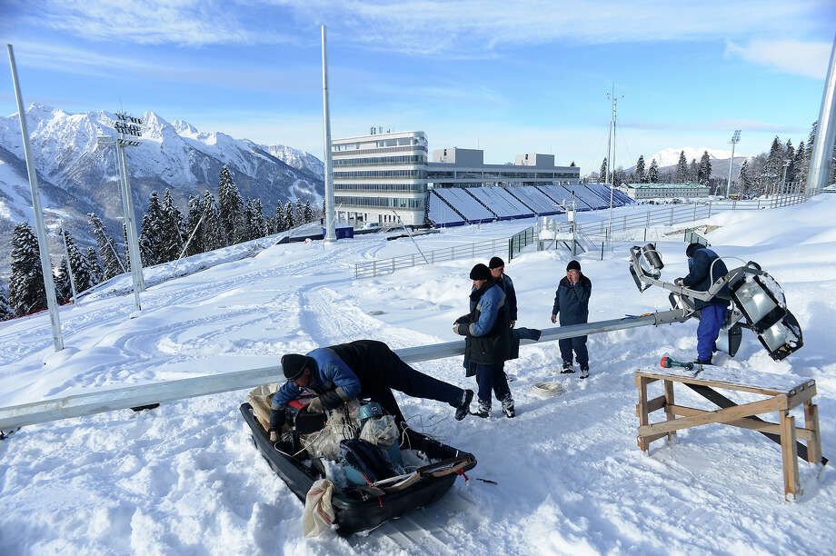 A workers prepare a lamp on the shooting range of the Laura Cross Country and Biathlon Center in Russian Black Sea resort of Sochi on February 3, 2013. Photo: KIRILL KUDRYAVTSEV, AFP/Getty Images / 2013 AFP