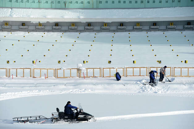 A workers remove the snow on the shooting range of the Laura Cross Country and Biathlon Center in Russian Black Sea resort of Sochi on February 3, 2013. Photo: KIRILL KUDRYAVTSEV, AFP/Getty Images / 2013 AFP
