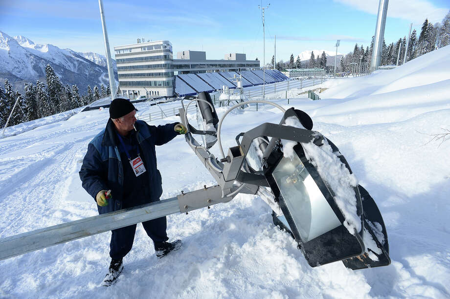 A worker prepares a lamp on the shooting range of the Laura Cross Country and Biathlon Center in Russian Black Sea resort of Sochi on February 3, 2013. Photo: KIRILL KUDRYAVTSEV, AFP/Getty Images / 2013 AFP