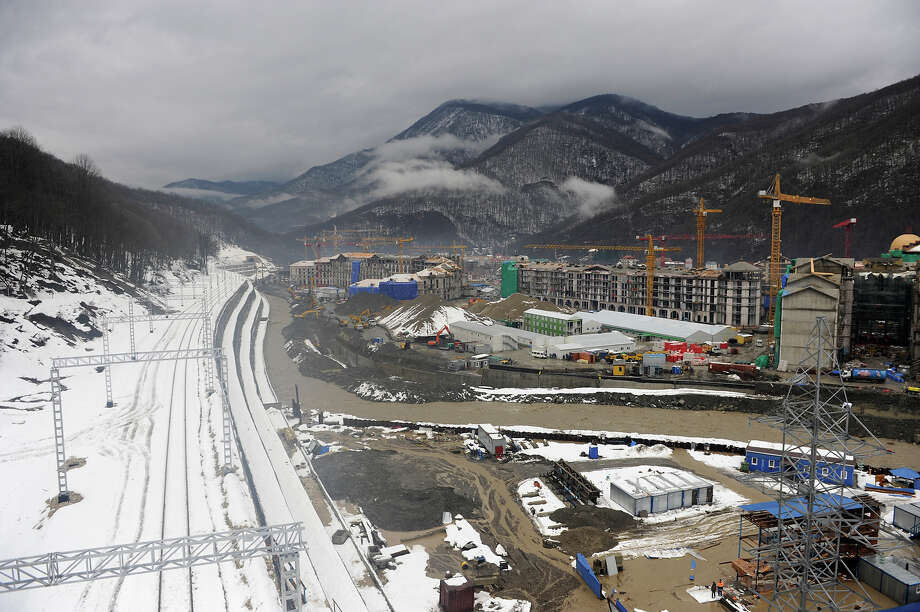 A picture taken on January 23, 2013, shows a railway and the construction site of the work on the Media Village for 22nd Winter Olympic Games in the Russian Black Sea resort of Sochi. One year before Russia kicks off the 22nd Winter Olympic Games on February 7, 2014, its host city Sochi is one of the world's biggest construction sites, with works proceeding on schedule but declared a disaster by environmentalists. Photo: AFP, AFP/Getty Images / 2013 AFP