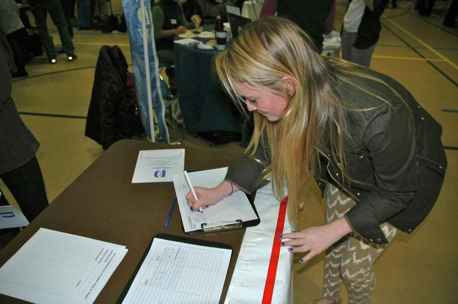 Darien High School Sophomore Lindsey Green signs up to volunteer for Person-to-Person youth group during the annual volunteer fair at DHS Friday, Feb. 1. Photo by Mac McDonough Photo: Contributed Photo