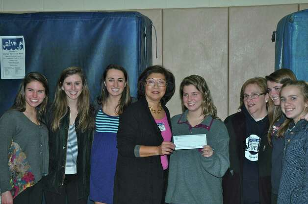 Kaye Leong of Darien Rowayton Bank presents a check for $300 toward The Depotís annual wish list. From left, Darien High School students Eliza Wisinski, Jenny Bealle and Phoebe Cush, Leong, Morgan Malvisi, Depot Program Director Janice Marzano, Parker Hamill and Cammie Lattimer during the annual volunteer fair at DHS Friday, Feb. 1. Photo by Mac McDonough Photo: Contributed Photo