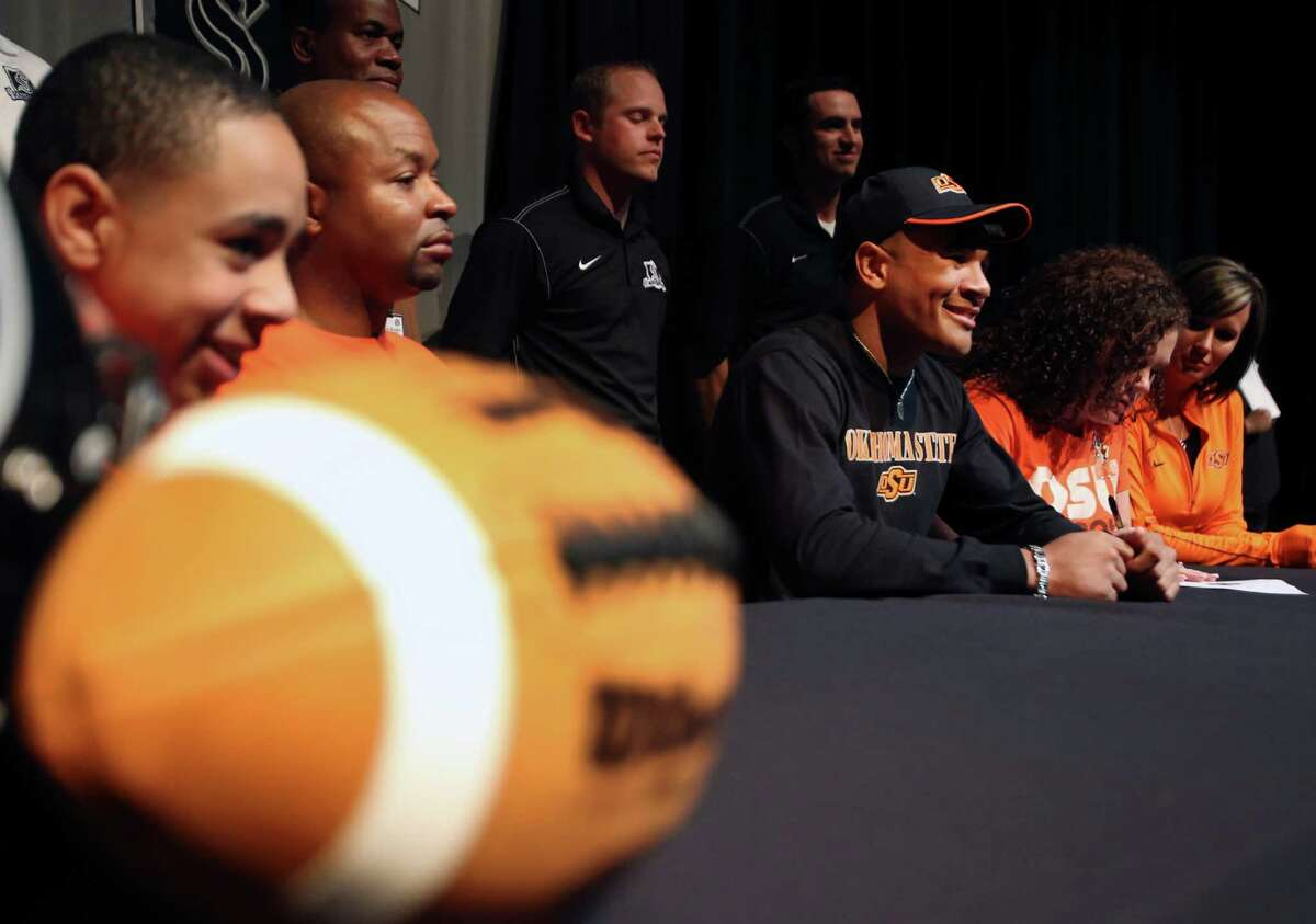 Steele High School football player Jordan Sterns, wearing hat and surrounded by his family and coaches, smiles Wednesday Feb. 6, 2013 after signing his letter of intent on National Signing Day to play football at Oklahoma State University.