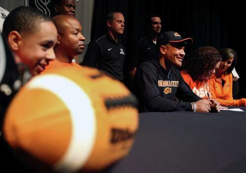 Steele High School football player Jordan Sterns, wearing hat and surrounded by his family and coaches, smiles Wednesday Feb. 6, 2013 after signing his letter of intent on National Signing Day to play football at Oklahoma State University. Photo: William Luther, San Antonio Express-News / © 2013 San Antonio Express-News