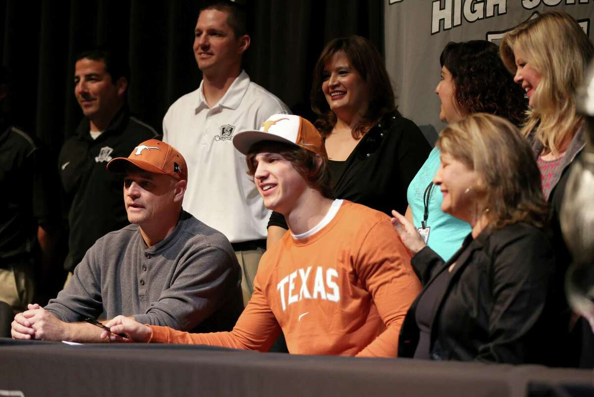 Steele High School football player Erik Huhn, front center, flanked by his father, Jeff Huhn and his mother, Sandy Huhn, smiles Wednesday Feb. 6, 2013 after signing a letter of intent on National Signing Day to play football at the University of Texas.