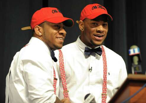 Grayson High School football player Robert Nkemdiche, right, the nation's top recruit, is congratulated by his brother Denzel during Robert Nkemdiche's announcement to play college football for Ole Miss, at a Grayson, Ga., signing ceremony Wednesday Feb. 6, 2013. Denzel Nkemdiche also plays for the Rebels. (AP Photo/David Tulis) Photo: Dave Tulis, Associated Press / FR170493 AP