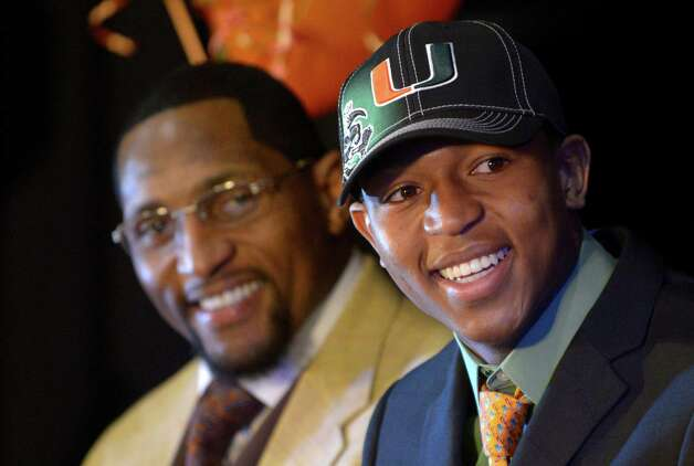 Ray Lewis III, right, smiles as he is introduced during a national signing day ceremony in the Lake Mary Prep auditorium as his father, former Baltimore Ravens linebacker Ray Lewis Jr., watches in Lake Mary, Fla., Wednesday, Feb. 6, 2013. Lewis signed a letter of intent to play football at the University of Miami, where his father also played college football. (AP Photo/Phelan M. Ebenhack) Photo: Phelan M. Ebenhack, Associated Press / FR121174 AP