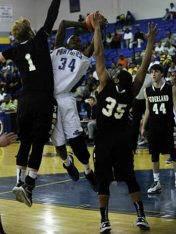 Ozen player Wayne Wyngard,#34, puts it up for two over Nederland players Colton Weisbrod, #1, and Jamiere Rogers, #35, during the Ozen High School boys basketball game against Nederland High School on Tuesday, February 5, 2013, at Ozen High School.  Nederland won over Ozen 50 - 45. Photo taken: Randy Edwards/The Enterprise