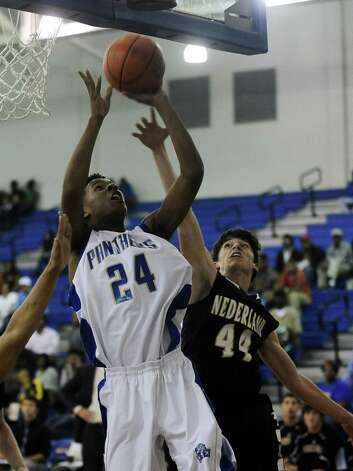 Ozen player Christian Bolton, #24, takes the rebound and puts it up for two during the Ozen High School boys basketball game against Nederland High School on Tuesday, February 5, 2013, at Ozen High School.  Nederland won over Ozen 50 - 45. Photo taken: Randy Edwards/The Enterprise