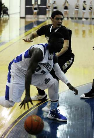 Ozen player Jordan Hunter, #23, drives to the goal during the Ozen High School boys basketball game against Nederland High School on Tuesday, February 5, 2013, at Ozen High School.  Nederland won over Ozen 50 - 45. Photo taken: Randy Edwards/The Enterprise