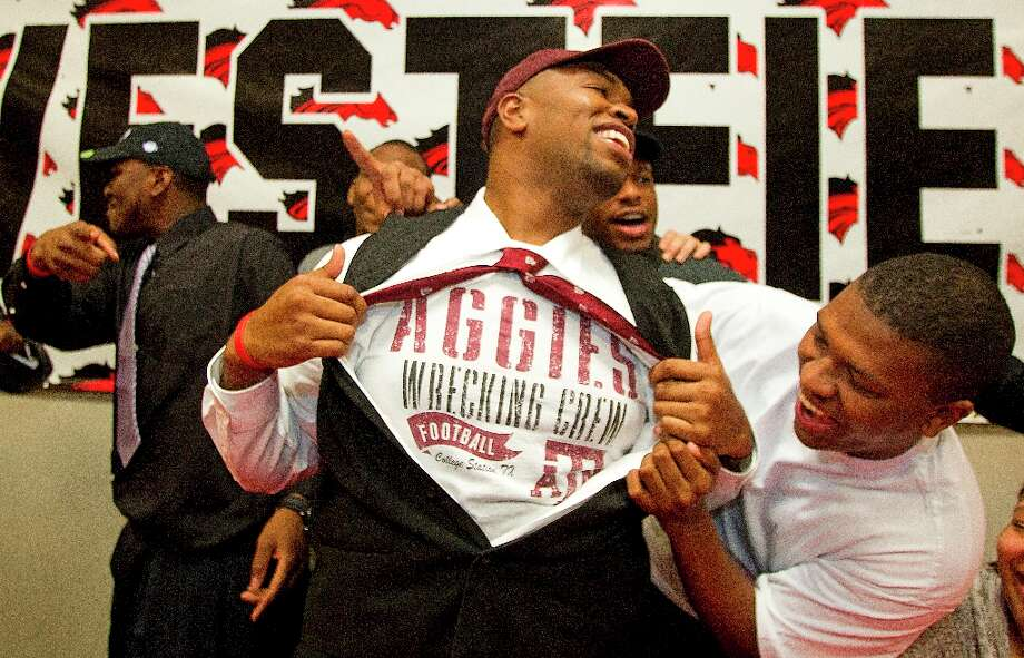 Texas A&M signee Hardreck Walker and his brother Chris Hall, right, laugh as Hardreck shows off an Aggies t-shirt during a National Letter of Intent signing ceremony at Westfield High School on Wednesday. Photo: Brett Coomer / © 2013 Houston Chronicle