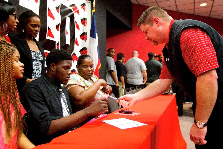 Westfield High School football coach Corby Meekins, right, hands a pen to Trinity Valley College signee Maurice Anderson during a National Letter of Intent signing ceremony on Wednesday. Photo: Brett Coomer / © 2013 Houston Chronicle