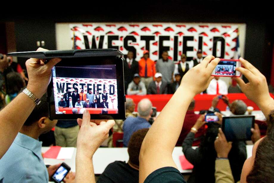 College-bound Westfield High School football players are seen on the screens of mobile devices as they are photographed during a National Letter of Intent signing ceremony on Wednesday. Photo: Brett Coomer / © 2013 Houston Chronicle