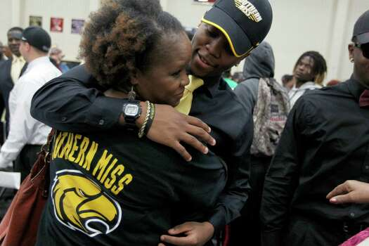 Hightower High School's Kelsey Douglas gets a hug from his mother Ingrid Douglas as he made his commitment to play football at Southern Miss during a signing day ceremony at the Buddy Hopson Field House Tuesday, Feb. 5, 2013, in Missouri City. Photo: Johnny Hanson, Houston Chronicle / © 2013  Houston Chronicle