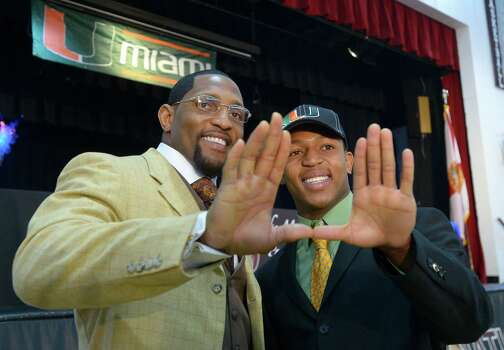 Ray Lewis III, right, and his father, former Baltimore Ravens linebacker Ray Lewis Jr., make the U sign with their hands, representing the University of Miami, after a national signing day ceremony in the Lake Mary Prep auditorium in Lake Mary, Fla., Wednesday, Feb. 6, 2013. Lewis III signed a letter of intent to play football at the University of Miami, where his father also played college football. (AP Photo/Phelan M. Ebenhack) Photo: Phelan M. Ebenhack, Associated Press / FR121174 AP