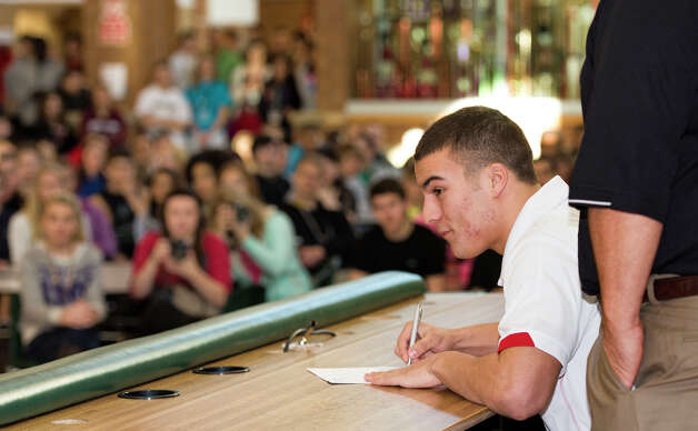 As a crowd of students, friends and family look on, Josh Banderas signs his letter to play football at Nebraska on National Letter of Intent signing day at Lincoln Southwest on Wednesday, Feb. 6, 2013. (AP Photo/Lincoln Journal Star, Ted Kirk) Photo: Ted Kirk, Associated Press / Lincoln Journal Star