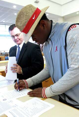 Reuben Foster signs a letter of intent to attend the University of Alabama and play college football as his coach Tim Carter looks on during National Signing Day on Wednesday, Feb. 6, 2013, in Auburn, Ala. (AP Photo/Butch Dill) Photo: Butch Dill, Associated Press / FR111446 AP