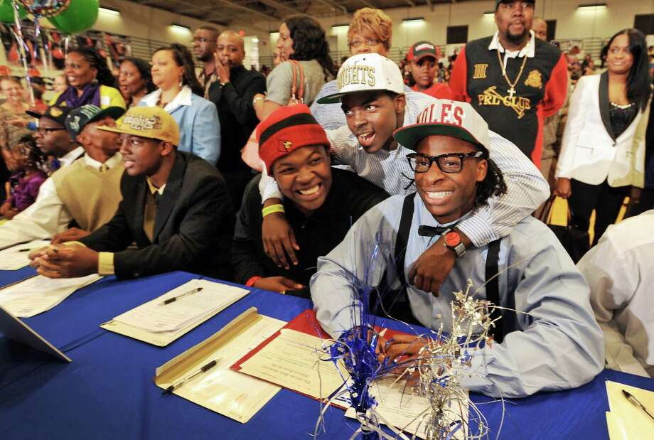 Dorian Killings, second from right, who is already enrolled at Central Florida,  joined teammates De'Asian Richardson, center, who signed with the University of Louisville and Tyrell Lyons, right, who signed with Florid State during National Signing Day ceremonies at First Coast High School, Wednesday, Feb. 6, 2013, in Jacksonville, Fla.  14 Students from First Coast High School in Jacksonville, Florida signed their letters of intent to play sports for a range of colleges during a rally in the school's gym.  T(AP Photo/The Florida Times-Union, Bob Self) Photo: Bob Self, Associated Press / The Florida Times-Union