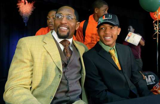 Ray Lewis III, right, poses for photos with his father, former Baltimore Ravens linebacker Ray Lewis Jr., during a national signing day ceremony in the Lake Mary Prep auditorium in Lake Mary, Fla., Wednesday, Feb. 6, 2013. Lewis signed a letter of intent to play football at the University of Miami, where his father also played college football. (AP Photo/Phelan M. Ebenhack) Photo: Phelan M. Ebenhack, Associated Press / FR121174 AP