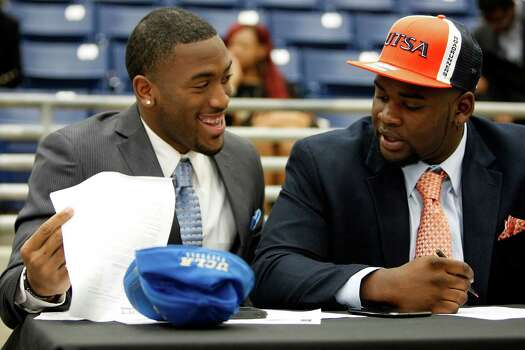 Fort Bend Marshall linebacker Deon Hollins Jr., left, who committed to play football at UCLA, shares a laugh with teammate Anthony Lee who committed to the University of Texas San Antonio during a signing day ceremony at the Buddy Hopson Field House Tuesday, Feb. 5, 2013, in Missouri City. Photo: Johnny Hanson, Houston Chronicle / © 2013  Houston Chronicle