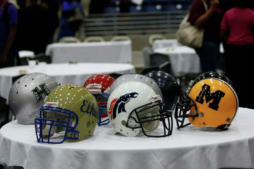 Fort Bend ISD High School football helmets sit on a table  during a signing day ceremony at the Budd