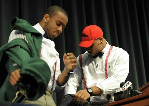 Grayson High School football player Robert Nkemdiche, right, the nation's top recruit, and his brother Denzel unveil their red suspenders during Nkemdiche's announcement to play college football for Ole Miss, at a Grayson, Ga., signing ceremony Wednesday, Feb. 6, 2013. (AP Photo/David Tulis) Photo: Dave Tulis, Associated Press / FR170493 AP