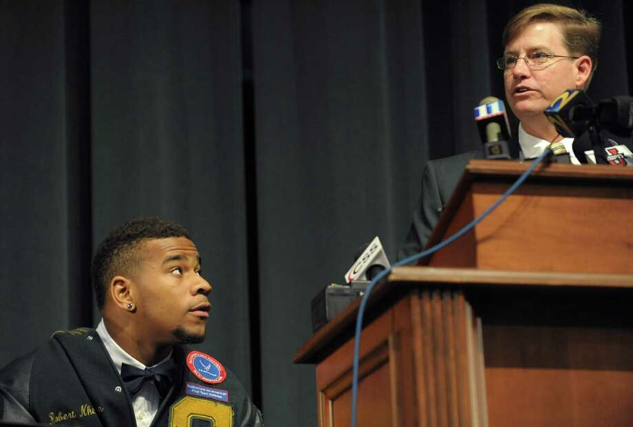 Grayson High School football player Robert Nkemdiche, left, the nation's top recruit, is introduced by Grayson High School head coach Mickey Conn as Nkemdiche announces his intent to play college football for Ole Miss during a signing day ceremony in Grayson, Ga., Wednesday Feb. 6, 2013. (AP Photo/David Tulis) Photo: Dave Tulis, Associated Press / FR170493 AP