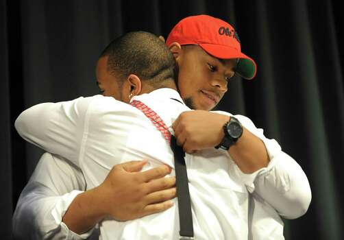 Grayson High School football player Robert Nkemdiche, right, the nation's top recruit, is congratulated by his brother Denzel during Nkemdiche's announcement to play college football for Ole Miss, at a Grayson, Ga., signing ceremony Wednesday Feb. 6, 2013. Denzel Nkemdiche also plays for the Rebels. (AP Photo/David Tulis) Photo: Dave Tulis, Associated Press / FR170493 AP