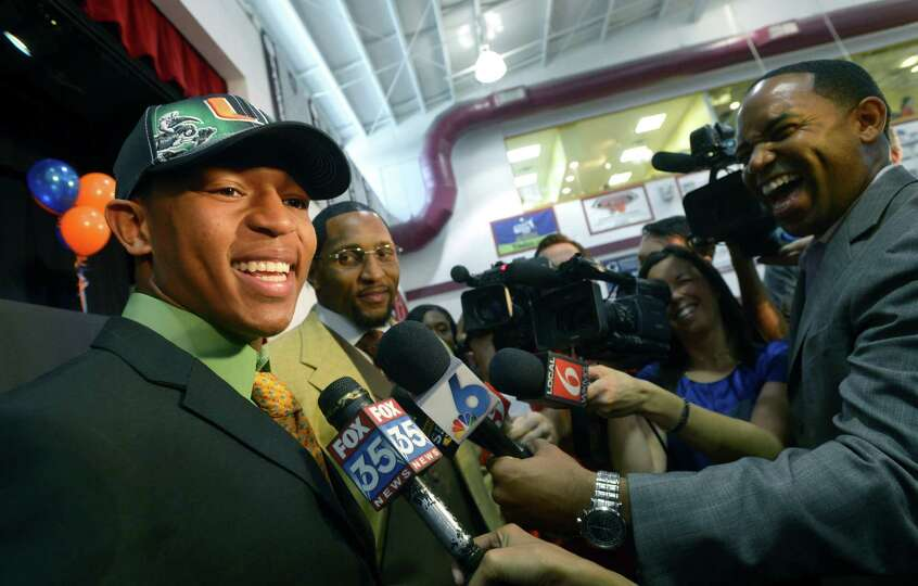 Ray Lewis III, left, answers questions from reporters during a national signing day ceremony in the