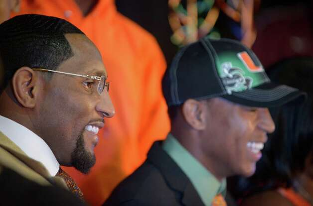 former Baltimore Ravens linebacker Ray Lewis Jr., left, smiles as his son Ray Lewis III signs his letter-of-intent form during a national signing day ceremony in the Lake Mary Prep auditorium in Lake Mary, Fla., Wednesday, Feb. 6, 2013. Lewis signed to play football at the University of Miami, where his father also played college football. (AP Photo/Phelan M. Ebenhack) Photo: Phelan M. Ebenhack, Associated Press / FR121174 AP