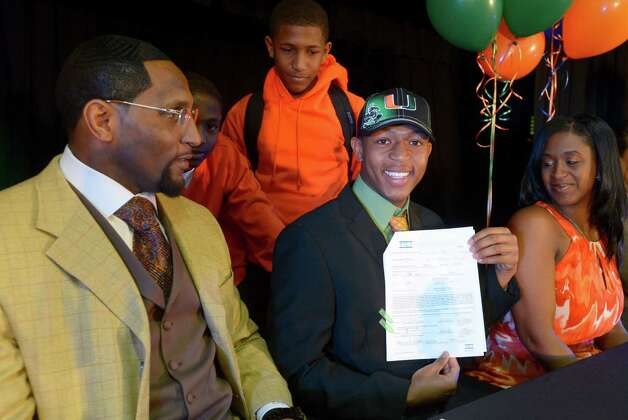 Ray Lewis III, second from right, shows his national letter-of-intent form as his father, former Baltimore Ravens linebacker Ray Lewis Jr., left, his mother Tatyana McCall, and brothers Rahsaan, 12, second from left, and Rayshad, 14, center, watch during a national signing day ceremony in the Lake Mary Prep auditorium in Lake Mary, Fla., Wednesday, Feb. 6, 2013. Lewis signed a letter of intent to play football at the University of Miami, where his father also played college football. (AP Photo/Phelan M. Ebenhack) Photo: Phelan M. Ebenhack, Associated Press / FR121174 AP